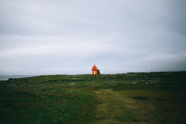 Lonely orange lighthouse on cloudy day in field