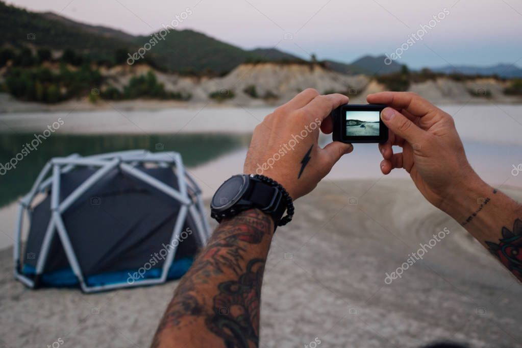 Hipster travel man makes photo of tent