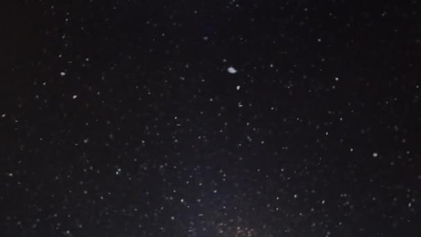 Na kameru v zimní noci pomalu padá sníh