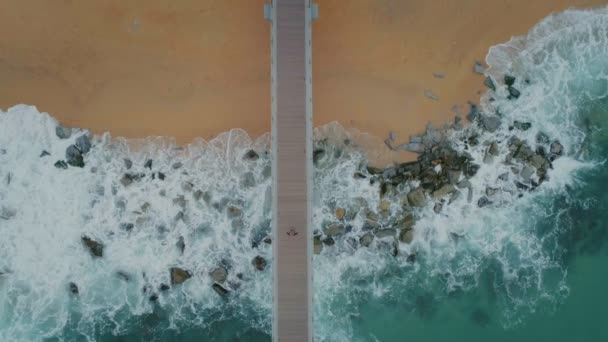 Top view from drone on pier on stormy beach