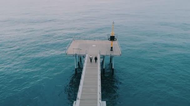 Two elderly women on morning walk on pier