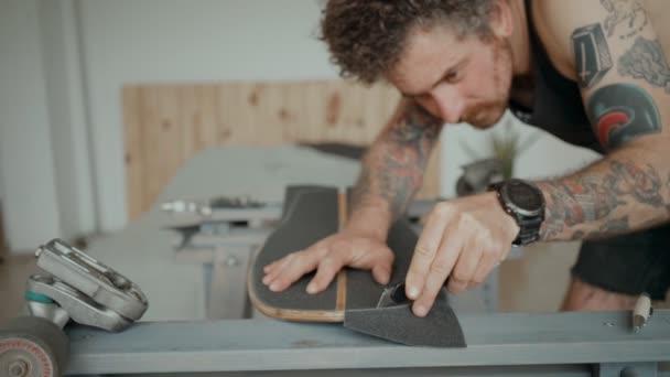 Skateboarder greift in Werkstatt nach Brettspielzeug