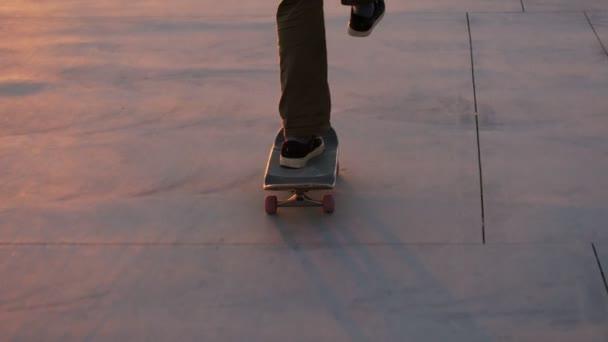 Millennial hipster skateboarder rides in sunset