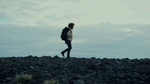 Young nomad traveller on epic mountain beach walk