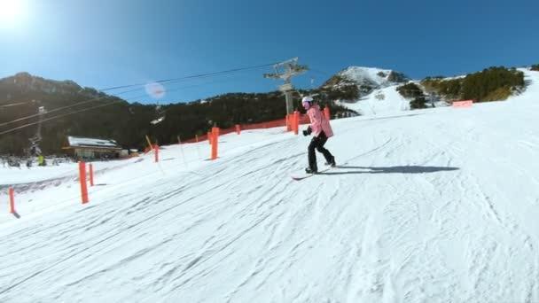 Junge Hipster-Snowboarderin auf Sonnenhang