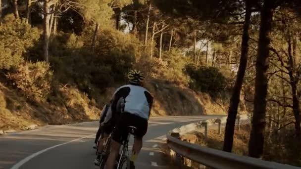 Cyklisté jezdi na horské cestě po západu slunce