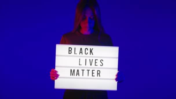 Mladá bílá žena držet černé životy hmota znamení