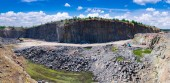 Photo Spectacular panoramic view of quarry open pit mining of granite stone. Process production stone and gravel. Quarry mining equipment.