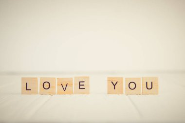 Message I love you spelled in wooden blocks standing on white wooden table. Valentines day background. Simplicity concept. Vintage tonning. Copy space