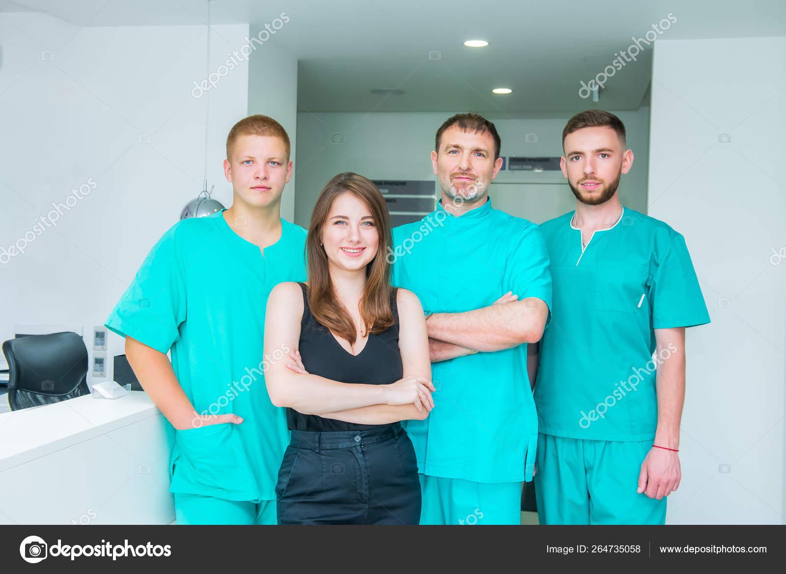 Smiling portrait team in uniform providing healthcare treatment in