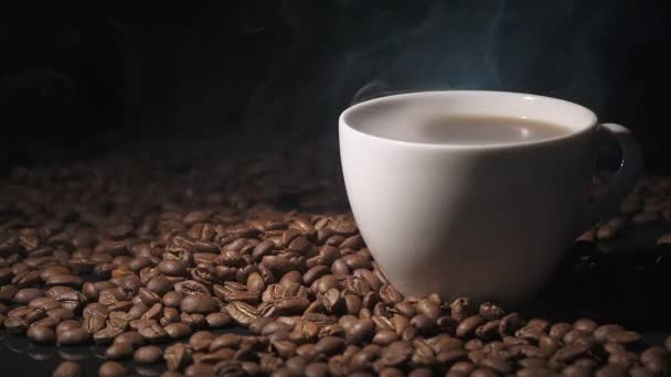 Cup of hot coffee, view of steam, coffee beans on a dark surface.