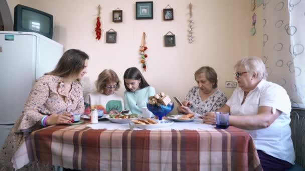 Péče o starší lidi. Dobrovolníci dívky učí elderlys Zenske používat smartphone, domácí interiér.