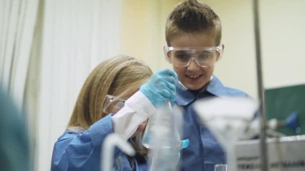 Laboratorní, školačka a školák v ochranné brýle nalije kapalina do zkumavky, chemické zkušenosti, výchova dětí
