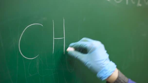 Chemistry lesson, a schoolboy writes a chemical formula in chalk on a blackboard.