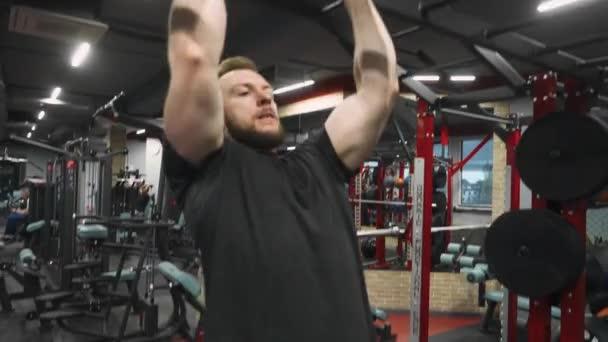 Man pulls himself up on a horizontal bar, strength training.