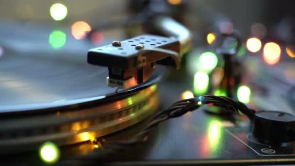 A lejátszó Dj lemezjátszó bakelit közelről. A forgó lemez és a toll és a tű közelről. Hurok. ragyogó bokeh fények ünnepi hangulat ünnepek koncepció