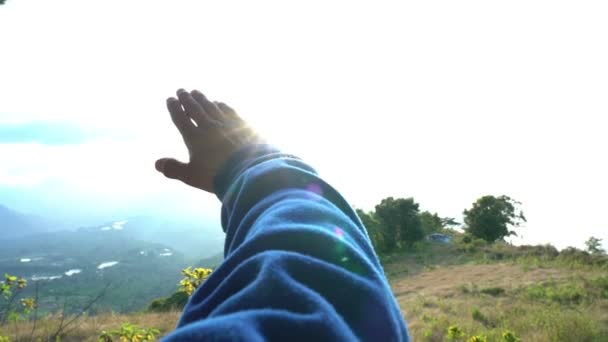 Grasping the sun with hand slow motion. Male hand against a sun and sky background, grasping the sun and letting sunlight pass through in mountain landscape
