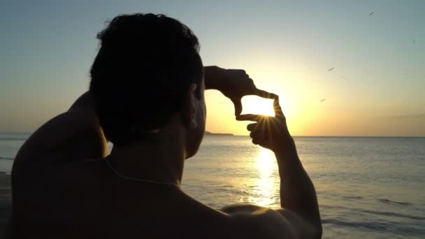 Young man with curly hair making photo frame with his hands at amazing sunset on the beach