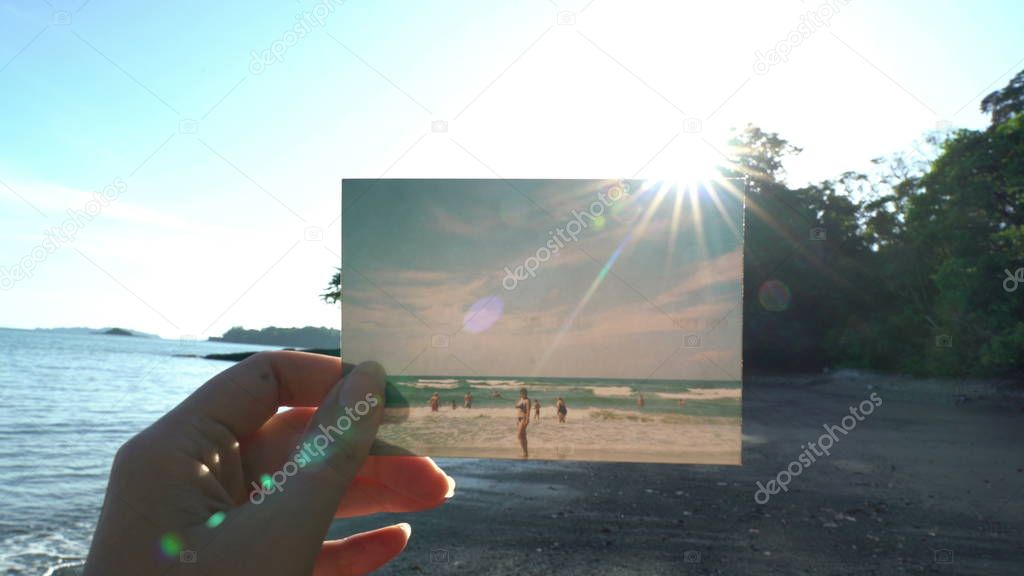 Close up hand holding photograph in front of beautiful tropical beach travel concept. Sun shining