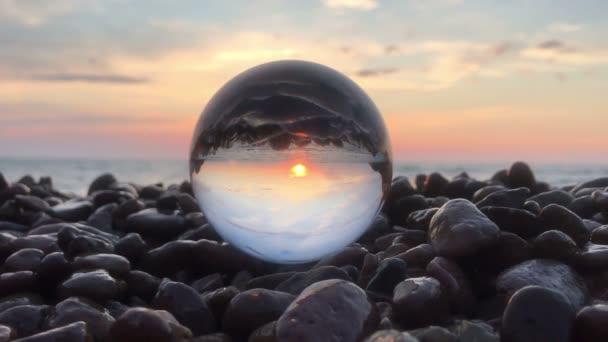 Beutiplné pozorování západu slunce uvnitř křišťálové koule na kamenech, slunce nad vodou, pláž, krajina
