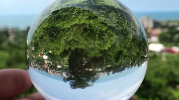 ruka držící kouzelnou krystovou kouli nad krásnou krajinnou krajinu, cestovní koncept