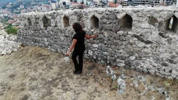 woman traveller investigating old ruins in ancient castle, discover history, aerial shot from drone