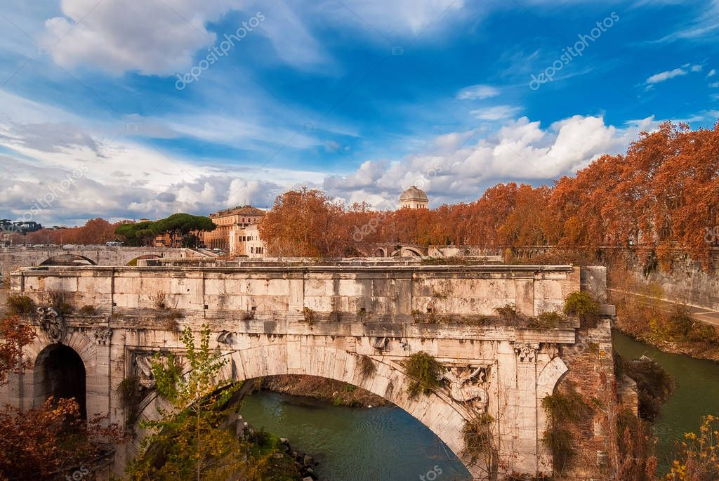 Autumn and foliage in Rome. Red and yellow leaves near Tiber Island with ancient bridge, in the city historic center