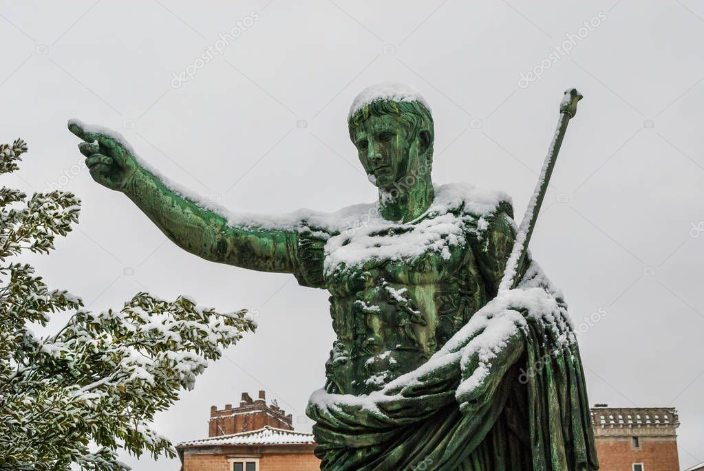 Frozen roman emperor. Caesar Augustus bronze statue along Imperial Forum covered by snow, a very rare event in Rome