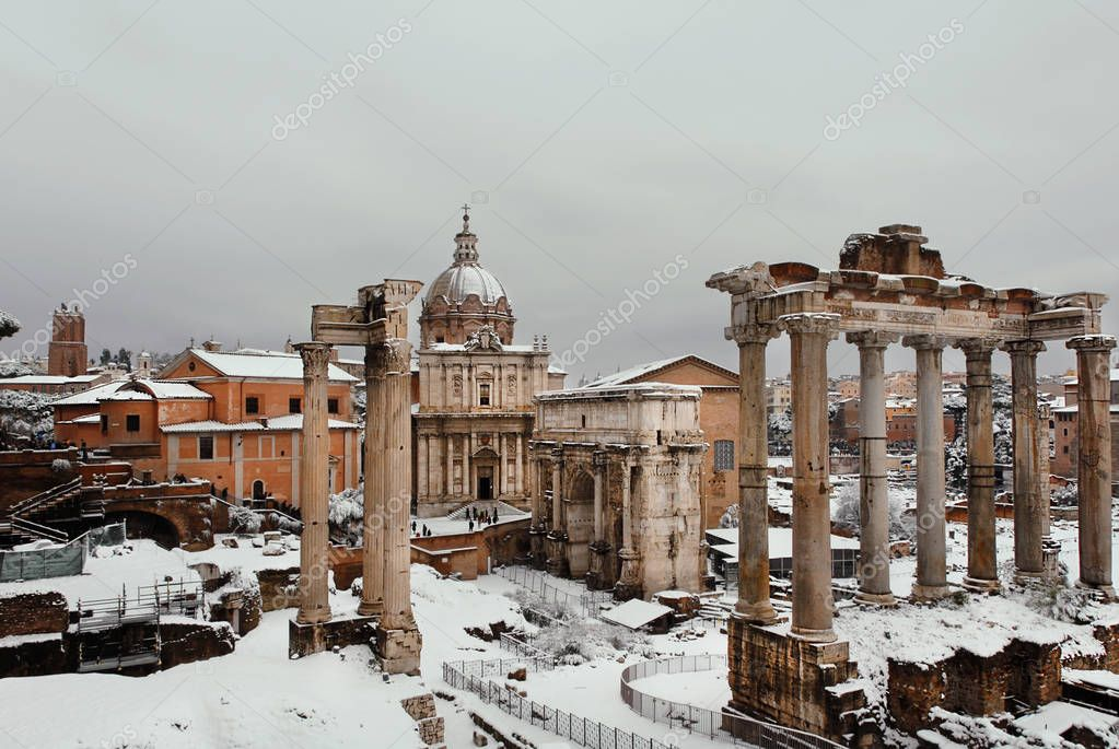 Winter in Rome. View of frozen Roman Forum ancient ruins and baroque church covered with snow