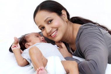 Cheerful young mother playing with newborn baby