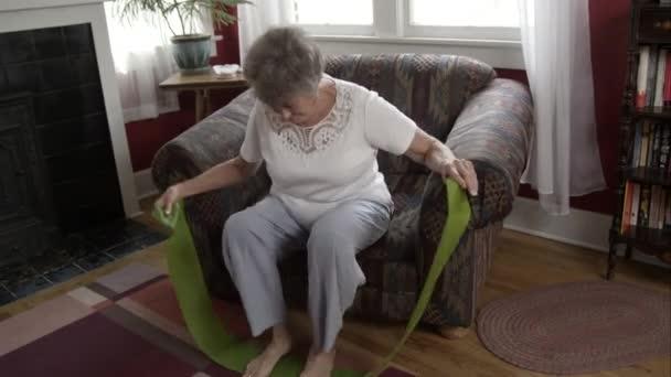Starší žena, která dělá cvičení s elastickým pásem doma.