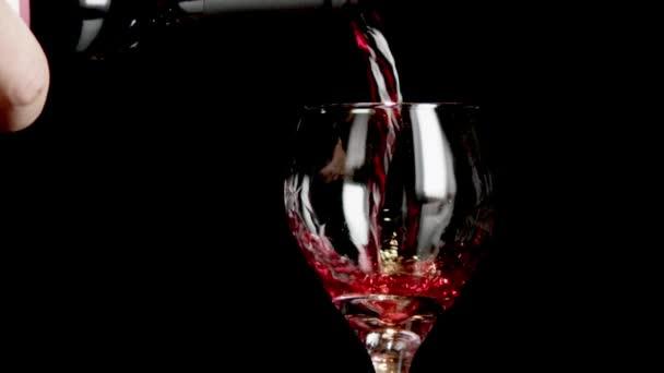 Prolitá sklenice červeného vína, které bylo nalito černým pozadím.