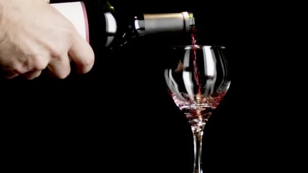 Těsná střela z skleničky vína, které bylo nalito černým pozadím.