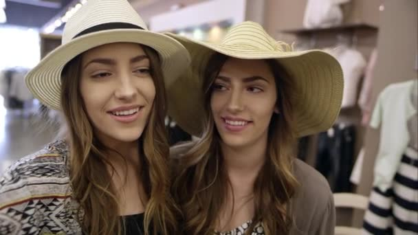 Teenage twins recording themselves as one kisses the others cheek in a clothing store.
