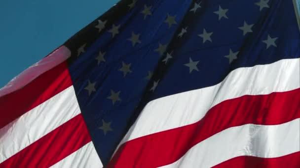 Big American Flag waving in wind against the sky.
