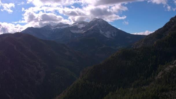 Vzdušný výhled na horské vrstvy a zasněžený horský vrchol s lehkým sněžným propadajícím.