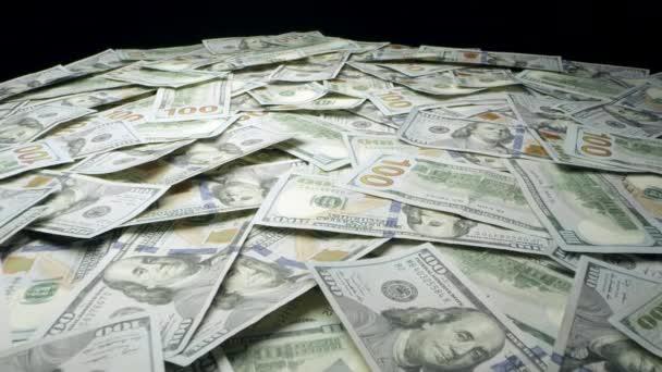 Ein großer Haufen Geld auf dem Tisch, der sich über die 100-Dollar-Scheine bewegt.