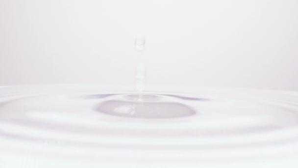 Goccia di liquido che spruzza sulla superficie dellacqua creando un ripple come le onde di rimbalzo indietro