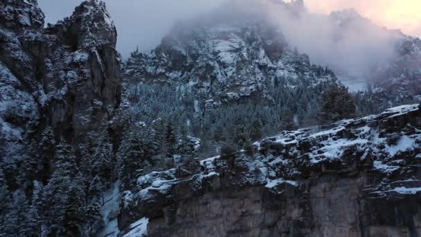 Posouvání letecký pohled na rozeklané útesy v zimě lesní krajině, jak slunce zapadá a mraky pokrývají vrcholky hor