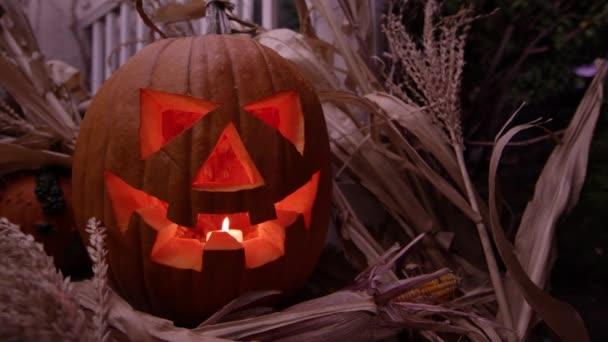 Jack olantern a gyertya pislákoló tornácon, körülvéve a kukorica szára során halloween sütőtök.