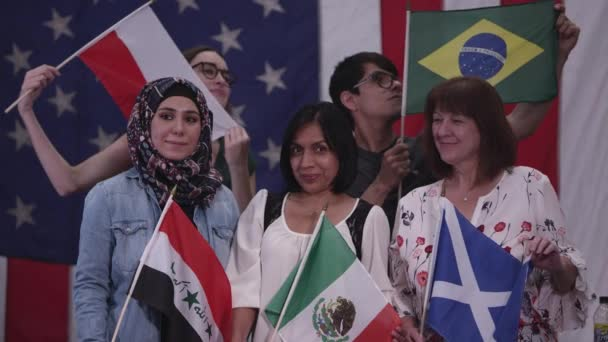 Group of people with different ethnicities holding flags from various countries they have heritage from.