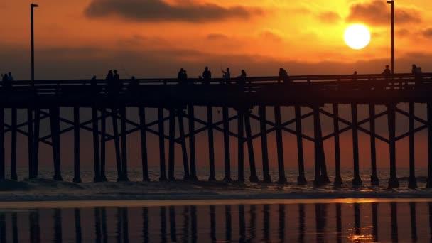 Lidé chodící přes molo během barevného západu slunce na Newport Beach.