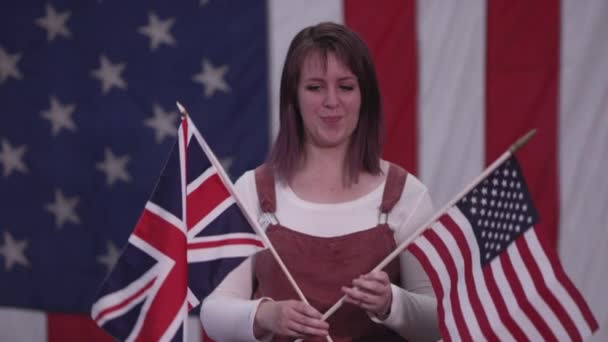 Woman holding up the Union Jack Flag and American Flag as she stands in front of American Flag.