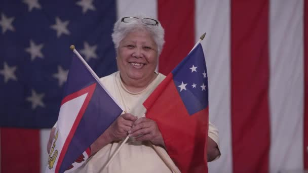 Woman holding Flag of Samoa and American Samoa as she stands in front of American Flag.