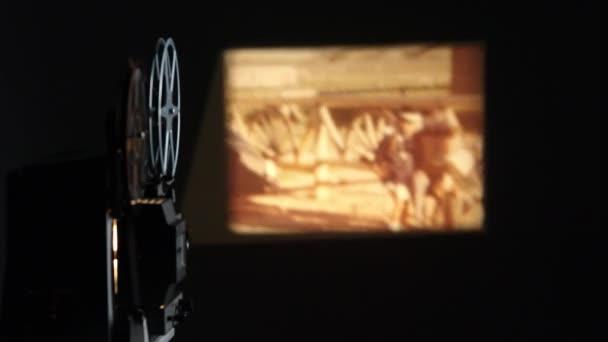 alter Projektor spielt Filmrolle an Wand mit Mädchen mit Mütze.