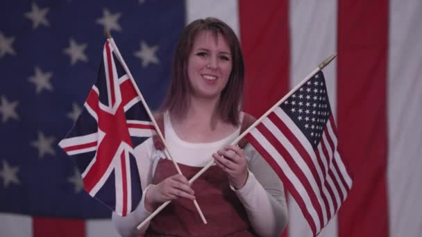 Woman holidng up American Flag and Union Jack Flag as she stands in front of American Flag.