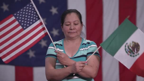 Woman holding up American Flag and Flag of Mexico as she stands in front of American Flag.