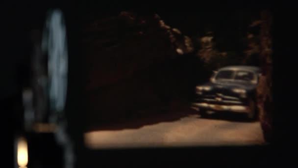 Ansicht des Projektors spielt alten Film von Autos, die auf einer engen kurvenreichen Straße fahren.