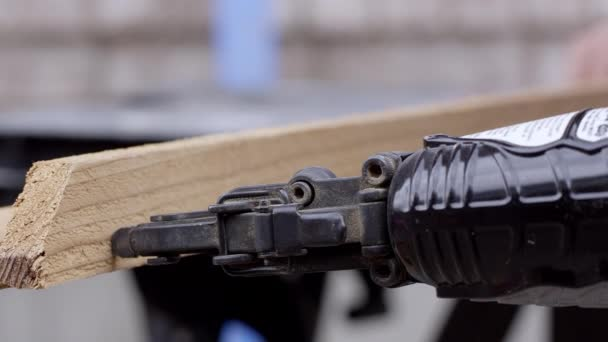 Up close view of nail gun putting nails in wood frame as it is build built.