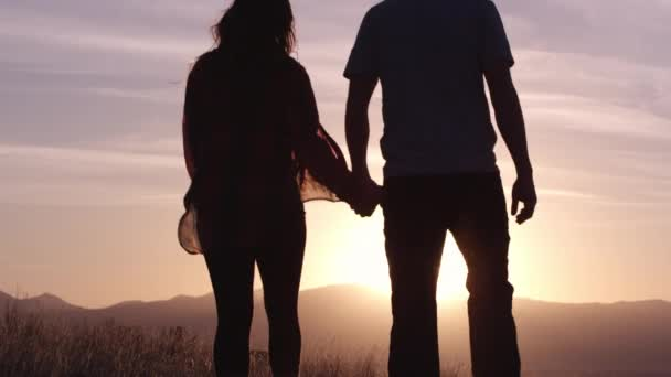 Young couple in love is resting in mountains at beautiful sunset